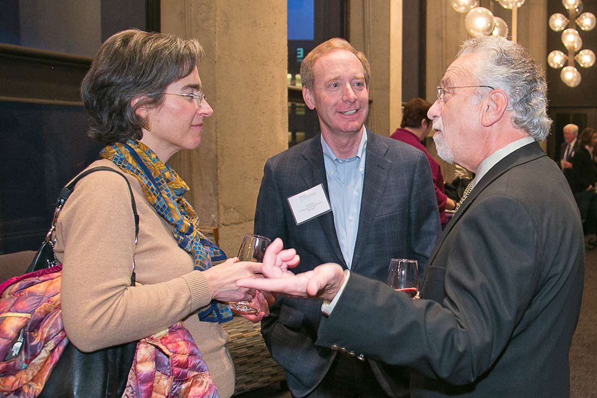 Norm Arkans, UW associate vice president, media relations and communications, talks with Irene Plenefisch, Microsoft government affairs director, and Brad Smith, Microsoft president and chief legal officer, at a pre-event reception.